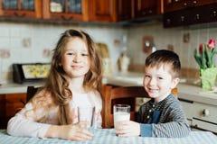 Los niños beben la leche y se divierten en la cocina en la mañana La hermana y el hermano preparan el cacao fotografía de archivo libre de regalías