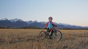 Los niños caucásicos uno caminan con la bici en campo de trigo Muchacha que camina el ciclo anaranjado negro en fondo de nevoso h metrajes