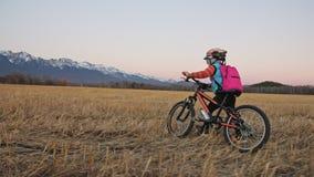 Los niños caucásicos uno caminan con la bici en campo de trigo Muchacha que camina el ciclo anaranjado negro en fondo de nevoso h almacen de metraje de vídeo