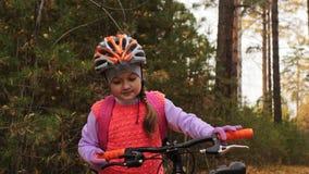 Los niños caucásicos uno caminan con la bici en parque del otoño La niña que camina el ciclo anaranjado negro en niño del bosque  almacen de metraje de vídeo