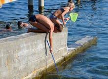 Los niños cogen una red de pequeños pescados en agua de mar fotos de archivo