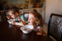 Los niños comen la consumición de la familia del desayuno Fotos de archivo