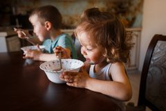 Los niños comen la consumición de la familia del desayuno Imagen de archivo libre de regalías