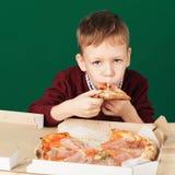 Los niños comen la pizza italiana en el café Escolar que come la pizza Foto de archivo