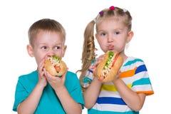 Los niños comen los perritos calientes Foto de archivo libre de regalías