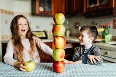 Los niños comen manzanas y se divierten en la cocina en la mañana foto de archivo