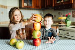 Los niños comen manzanas y se divierten en la cocina en la mañana fotos de archivo libres de regalías