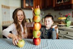 Los niños comen manzanas y se divierten en la cocina en la mañana imágenes de archivo libres de regalías