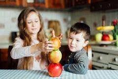 Los niños comen manzanas y se divierten en la cocina en la mañana imagen de archivo libre de regalías