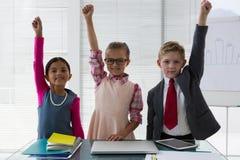 Los niños como ejecutivo de operaciones que sonreía con sus manos aumentaron en la oficina Imagenes de archivo