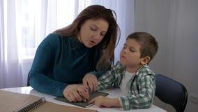 Los niños con deficiencias visuales de la educación, mamá enseñan al muchacho ciego del hijo a escribir la fuente de caracteres d almacen de video