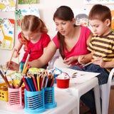 Los niños con el profesor drenan las pinturas en sitio del juego. Fotos de archivo