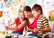 Los niños con el profesor drenan las pinturas en sitio del juego. Imágenes de archivo libres de regalías