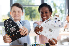 Los niños con el robot modelan la sonrisa en la cámara Imagenes de archivo