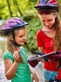 Los niños con la tableta montan la bicicleta que busca el mapa de Internet de la manera Fotos de archivo libres de regalías