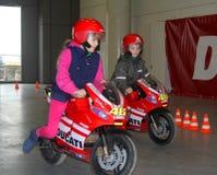 Los niños con las motocicletas que compiten con Foto de archivo