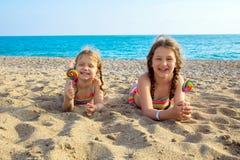 Los niños con las piruletas coloridas disfrutan de vacaciones de verano Fotos de archivo libres de regalías