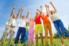 Los niños con los brazos para arriba se colocan derecho en fila foto de archivo