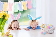 Los niños con los oídos del conejito en el huevo de Pascua cazan Imagen de archivo
