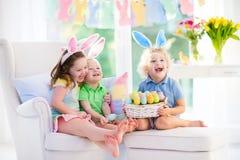 Los niños con los oídos del conejito en el huevo de Pascua cazan Fotografía de archivo libre de regalías
