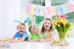 Los niños con los oídos del conejito en el huevo de Pascua cazan Foto de archivo