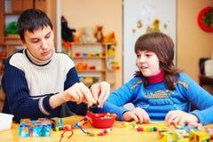 Los niños con necesidades especiales desarrollan sus capacidades finas de motor en centro de rehabilitación de la guardería foto de archivo libre de regalías