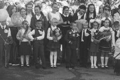 Los niños con los ramos de flores alistaron en la primera clase en la escuela en la inauguración del año escolar en el día de kno Imágenes de archivo libres de regalías