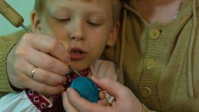 Los niños con su padre pintan los huevos de Pascua tradicionales almacen de metraje de vídeo