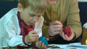 Los niños con su padre pintan los huevos de Pascua tradicionales metrajes