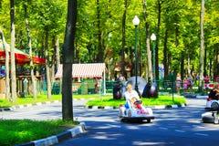 Los niños con sus padres conducen los coches eléctricos en parque Imágenes de archivo libres de regalías