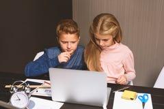 Los niños concentrados están estudiando cuidadosamente Foto de archivo libre de regalías