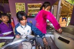 Los niños consiguen la comida en el tiempo del almuerzo en la escuela por cuidado de los niños del camboyano del proyecto para ay Foto de archivo libre de regalías