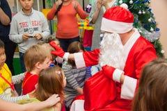 Los niños consiguen regalos de Navidad de Papá Noel Imagenes de archivo