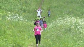 Los niños corren abajo de la colina en día de fiesta del día de pleno verano almacen de video