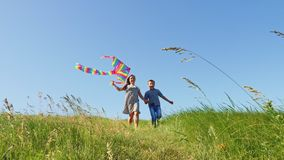 Los niños corren abajo de la colina verde con una cometa del vuelo almacen de metraje de vídeo