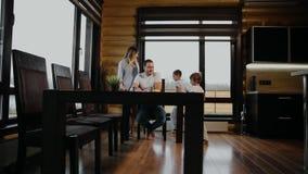 Los niños corren del dormitorio a la cocina para el desayuno, y allí de sentarse en los padres de una tabla Familia feliz, niños almacen de video