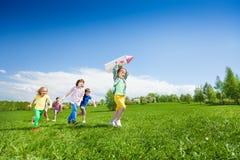 Los niños corren después del muchacho que sostiene el juguete del cartón del cohete Imagen de archivo