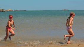 Los niños corren a lo largo del agua a lo largo de la línea de la resaca almacen de video