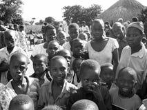 Los niños curiosos africanos de la muchedumbre que recolectan como ayudantes humanitarios de la ayuda llegan Foto de archivo