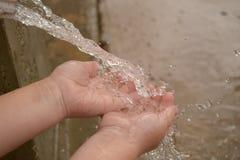 Los niños dan jugar en agua de un guttering Fotos de archivo libres de regalías