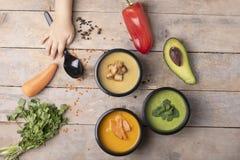 Los niños dan sostienen la cuchara cerca de las sopas del vegano en envases de comida, comida lista para comer fotos de archivo libres de regalías