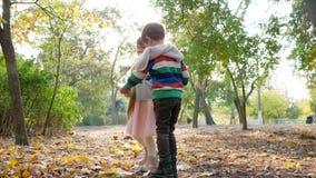 Los niños dan vuelta alrededor a detenerse las manos en parque del otoño en el día soleado en contraluz metrajes