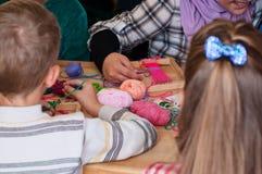 Los niños de Grupa aprenden tejer Imágenes de archivo libres de regalías