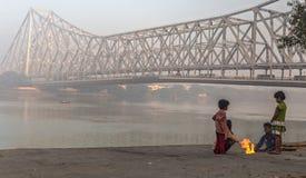 Los niños de la calle mantienen caliente en una mañana de niebla fría del invierno en el ghat de Mallick cerca del puente de Howr Foto de archivo libre de regalías