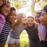 Los niños de la escuela abrazan la situación en un círculo, formato cuadrado imagenes de archivo