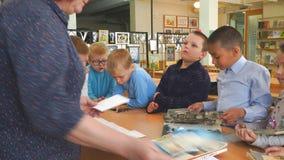 Los niños de la escuela con los libros se colocan al lado del escritorio del profesor almacen de metraje de vídeo