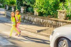 Los niños de la escuela primaria están cruzando la calle Imágenes de archivo libres de regalías