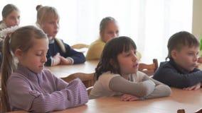 Los niños de la escuela se sientan en los escritorios almacen de metraje de vídeo