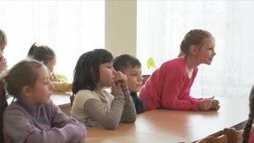 Los niños de la escuela se sientan en los escritorios almacen de video