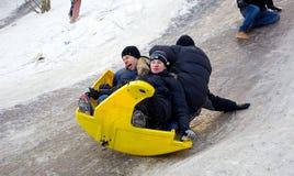 Los niños de la gente montan en la nieve del invierno sledding de las colinas Invierno que juega, diversión, nieve Fotos de archivo libres de regalías
